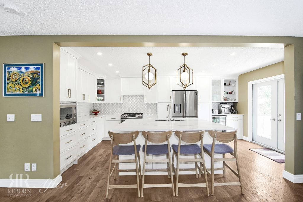 photos of remodeled kitchen, light accent cabinet, countertops with wooden chair, iron cage chandelier, modern appliances in NW, Calgary AB