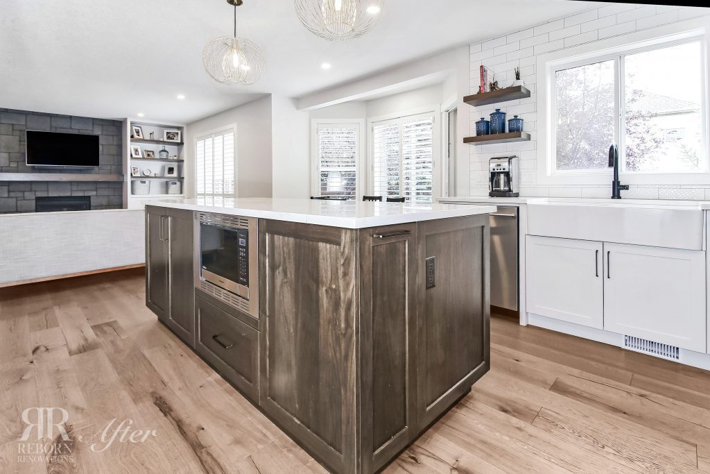Photo of modern kitchen that has wooden base cabinets with marble countertops, farmhouse sink in front of window, small chandeliers, in Calgary , AB CA