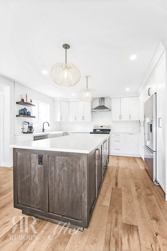 Photo of newly rebuilt kitchen, marble countertops, pendant light fixtures, in-line kitchen exhaust fans in SW Calgary AB