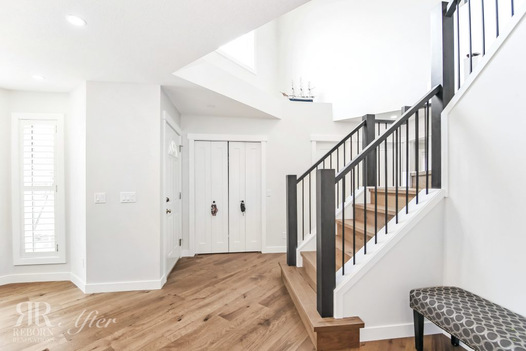 Photo of newly built living room, L-shade stairs with custom banisters, wooden floor, white painted door in Calgary AB, CA