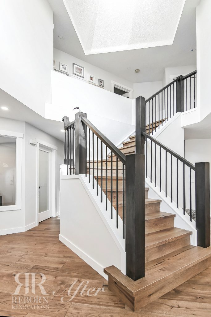 Photos of modern style white painted entryway, hard wood flooring, L-shaped staircase in South West Calgary, AB