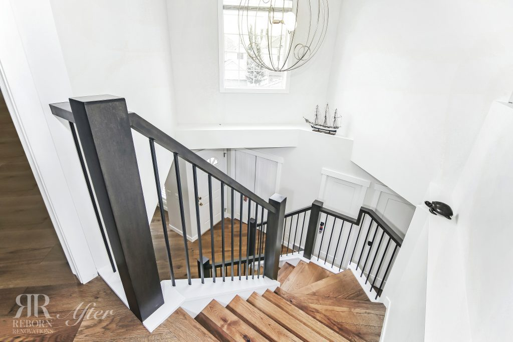 Photos of newly finished wooden stairs with metal banisters, white painted walls, wooden flooring in second floor in Soutwest, Calgary, AB, Canada