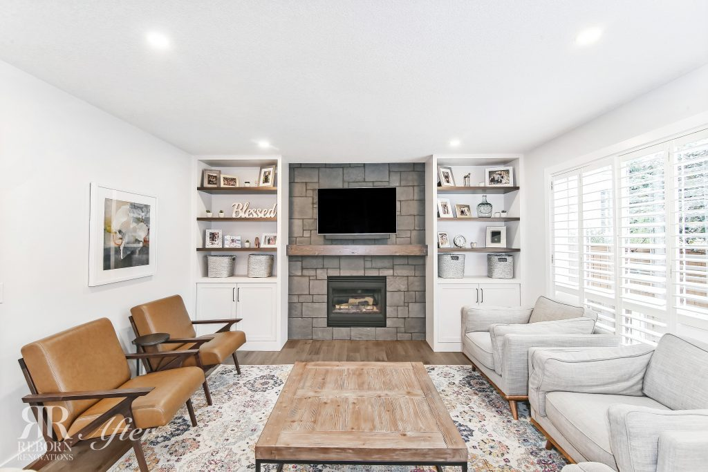 Photo of renovated white painted living room , shelves with cabinets bordering new fireplace with wooden shelf in South Calgary