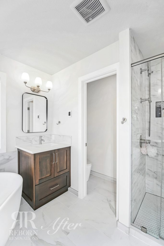Photo of newly built bathroom, wooden base cabinet with sink, white walls, separate toilet, rounded corner mirror, led vanity light in Strathcona Park Southwest, Calgary