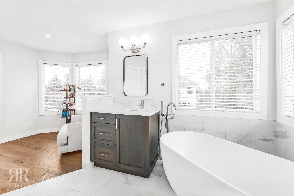 Photos of remodeled bathroom, light painted walls, wooden base cabinets with sink, led vanity lights, wooden floor and tiles, elegant bath tub in Calgary AB