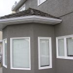 Vinyl Window Cladding installation in Calgary and grey stucco paint